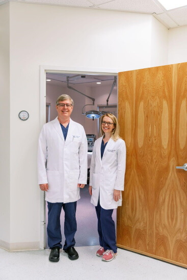 Dr. O'Neill and Dr. Swartz standing in front of the operating room